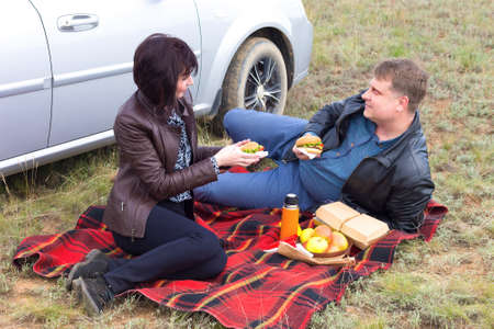 A man and a woman arranged a date in nature, a picnic on the steppe grass. Banque d'images