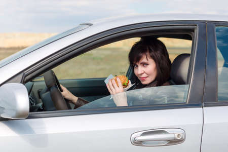 Woman with food in hand driving a car, Banque d'images