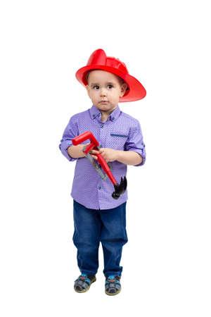 Three-year-old boy in a red helmet with toys in his hands, isolated.