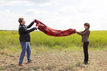 Husband and wife shaking dust and dirt off a blanket at a picnic. Banque d'images