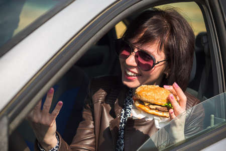 Woman with food in hand driving a car.