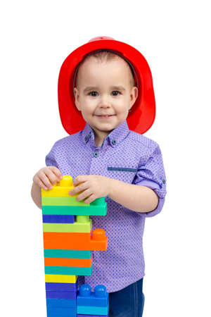 Three-year-old boy in a red helmet with toys in his hands isolated. Banque d'images