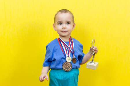 Little child dreams of sports victory, yellow background.