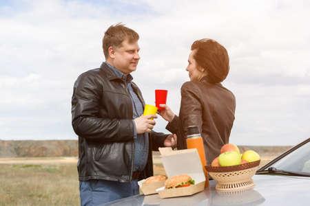 Adults had a romantic picnic near car.