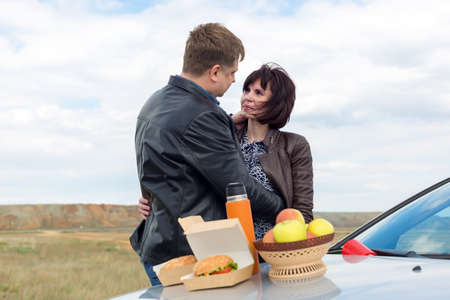 Adults had a romantic picnic near the car.