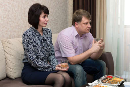 Husband and wife having dinner with watching TV in the house. Banque d'images