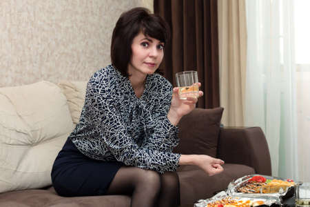 Pretty woman having dinner at home alone at a small table.