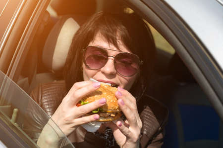 Happy young woman having lunch in the car. Sunglasses