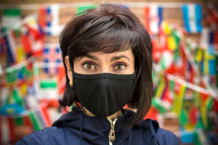 Adult woman in a medical mask on a wall background with a flag. Close-up