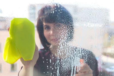 A 45-year-old brunette woman washes the window in the apartment. Blurred image, no focus.