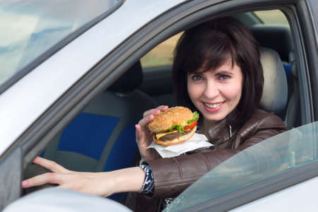 Happy young woman having lunch in the car.