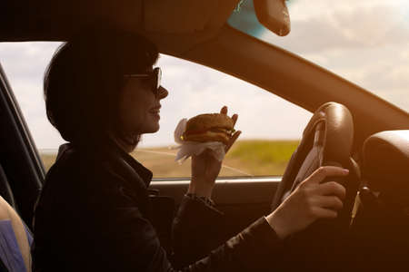 Woman driver eats and watches the road carefully at sunset Banque d'images