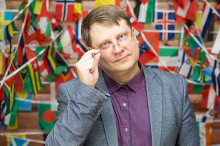 Dean of the Faculty of International Relations on the background of flags of different countries.