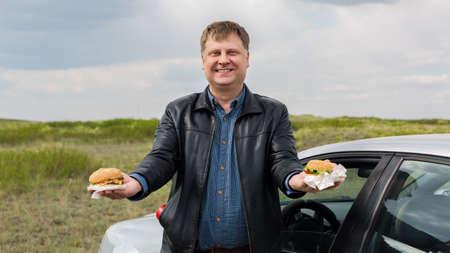 A man in the fresh air treats two hamburgers.,