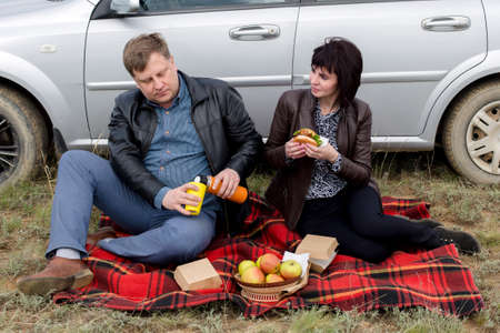 Adults in love with car travelers relax and have lunch near the car.