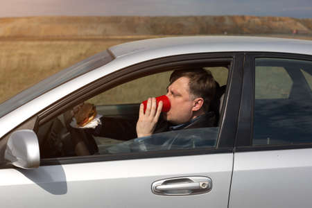 The manager eats lunch at the wheel in the car.