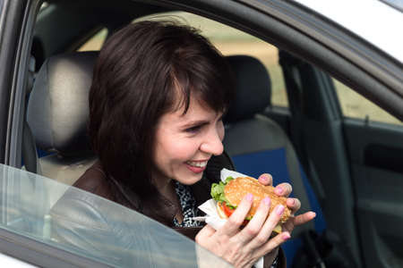 The taxi driver, laughing, in the car eats a juicy hamburger.