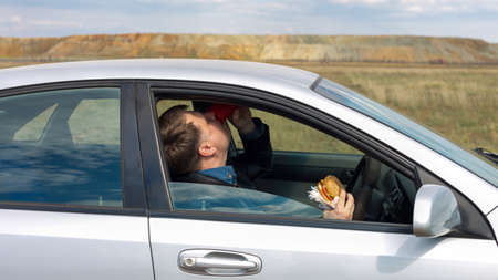 The manager eats lunch at wheel in the car.