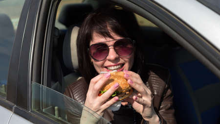 The taxi driver laughing in the car eats a juicy hamburger. Banque d'images