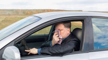 A sick driver wipes his nose with a handkerchief at the wheel of a car on way to the hospital.
