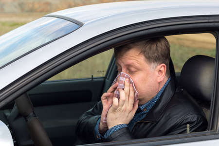 A sick driver wipes his nose with a handkerchief at the wheel of a car, on the way to the hospital.