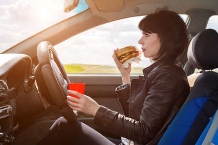 Businesswoman eats a burger on the way to work. Banque d'images