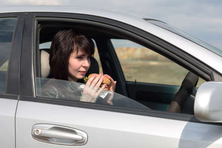 A woman with fast food at the wheel, the concept of poor nutrition in modern society. Banque d'images