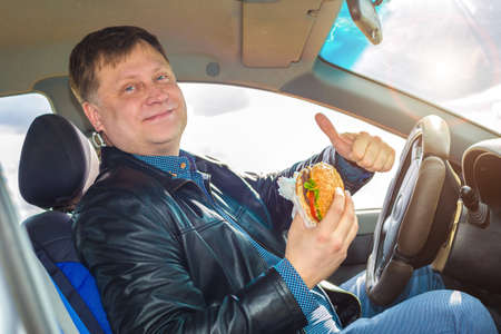 A very satisfied driver behind the wheel of a car enjoys a hamburger. Banque d'images