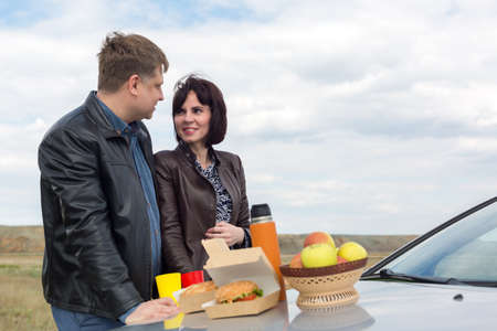 Romantic picnic in nature, on the hood of a car. Banque d'images