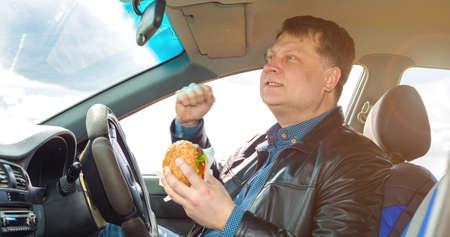 A very satisfied driver behind wheel of a car enjoys a hamburger.