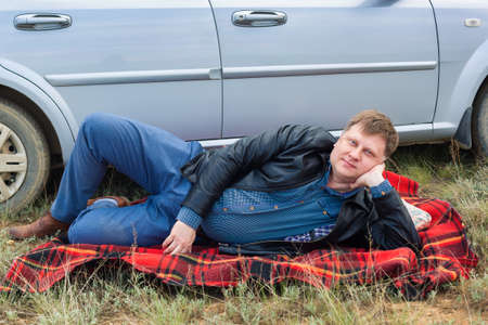 The tired driver lies on blanket near the car.