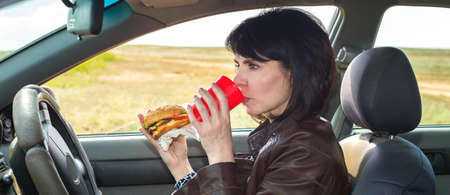Businesswoman eats a burger on way to work. Banque d'images