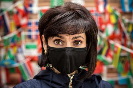 A woman wearing a protective mask and a blue jacket during the pandemic.