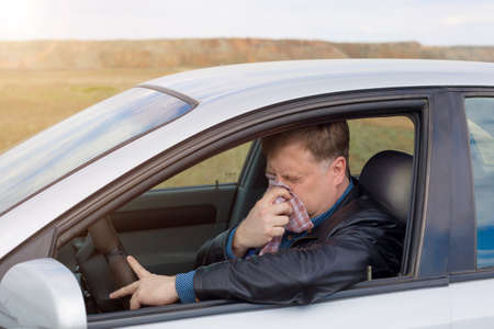 A man driving a car with a high temperature wipes his snot with a handkerchief. Banque d'images