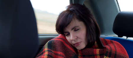The girl after a long road sleeps in the car covered with a blanket. Banque d'images