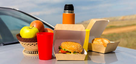 Lunch in nature on the hood of the car after a long trip. Banque d'images