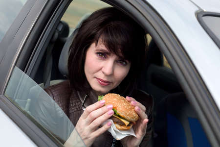 A woman in the car with a burger in her hands. Banque d'images