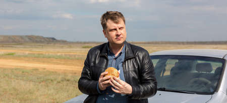 A thoughtful man in nature near the car with a burger in his hands. Banque d'images