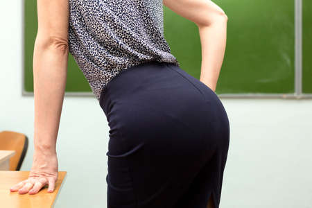 A young teacher coquettishly leaned her elbows showing her buttocks.