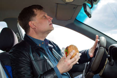A man with a hamburger in his hand at the wheel of a car honks at pedestrians.