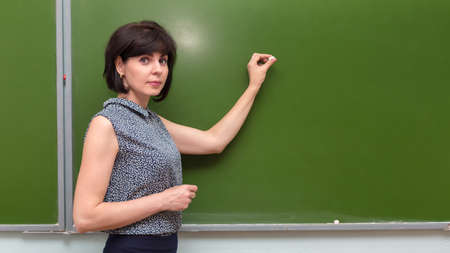 The teacher is standing in the classroom at the blackboard with chalk in her hand.