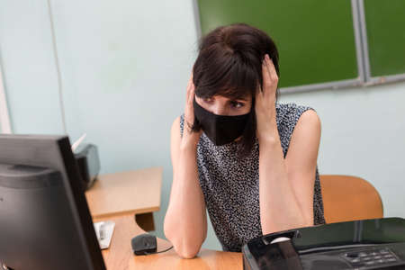 A tired teacher in a protective mask at table put her hands on her head.