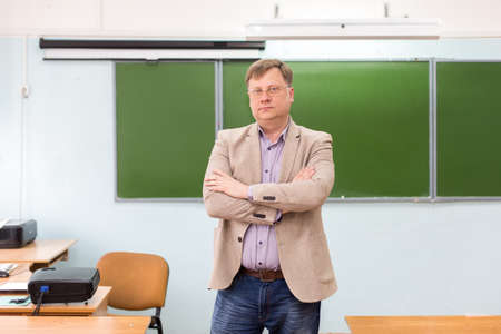 The serious headmaster stands in the classroom at blackboard with his arms folded.