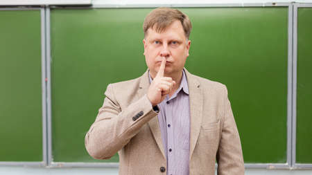 The male teacher gestures for silence in classroom.