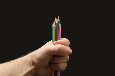 A pile of colored pencils in the artist's clenched fist.