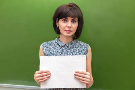 A teacher with a white sheet of paper stands at green blackboard copy space.
