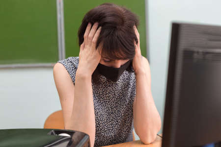 A tired teacher in a protective mask at the table put her hands on her head.