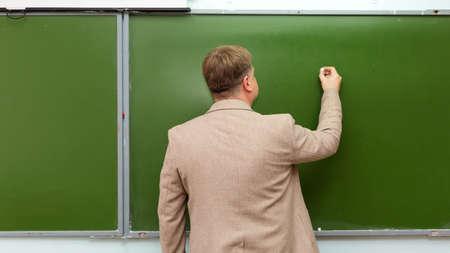 Math teacher writes chalk on blackboard copy space.