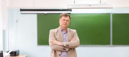 The serious headmaster stands in the classroom at the blackboard with his arms folded. Banque d'images