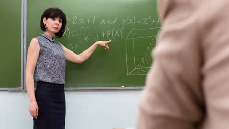 The teacher stands at the blackboard and asks the student to answer with a hand gesture.